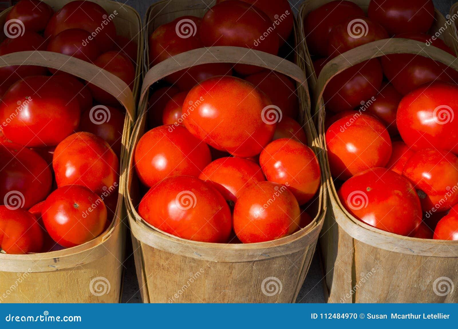 Tomates rouges lumineuses dans les paniers en bois d agriculteurs au marché