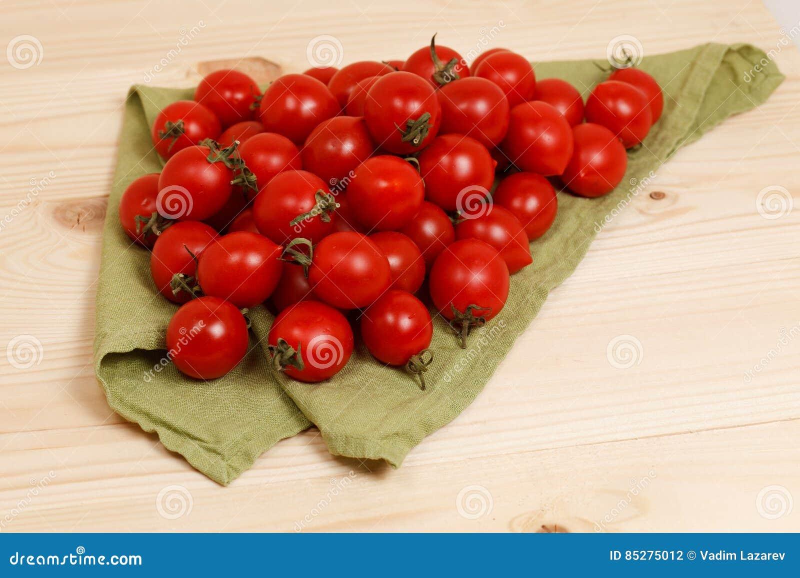 Tomates sur le fond en bois de tissu vert