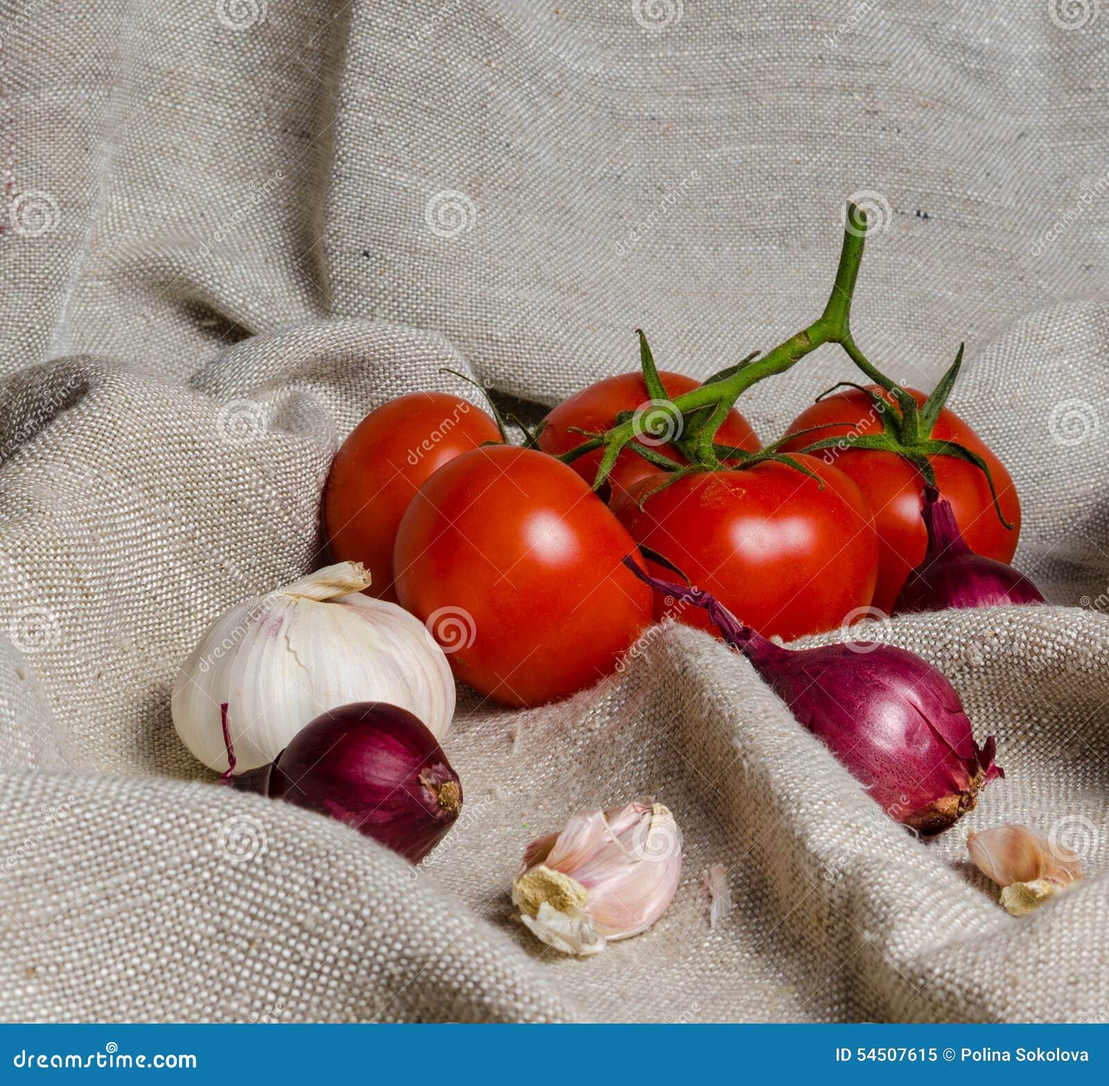 Tomates sur une branche, un oignon et un ail
