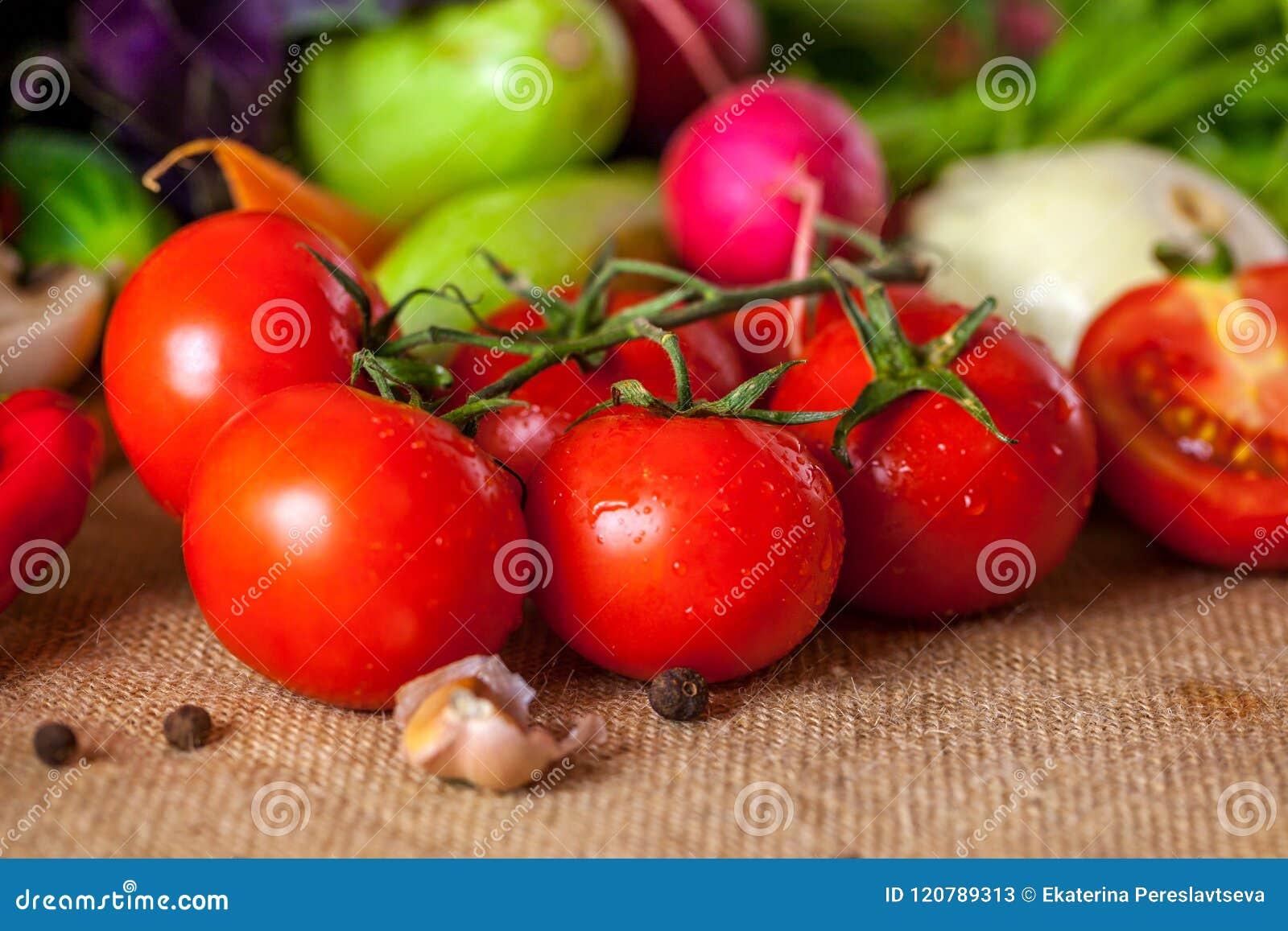 Tomates vermelhos e pimenta vermelha madura com gotas da água, conceito saudável do alimento