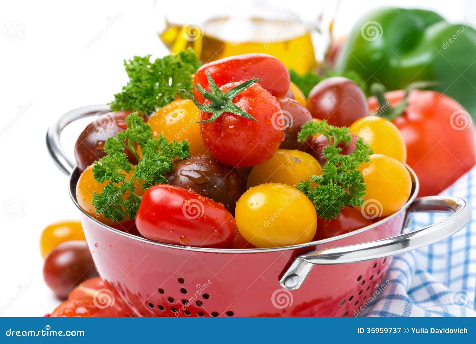 Tomates y verdes de cereza clasificados en un colador, primer