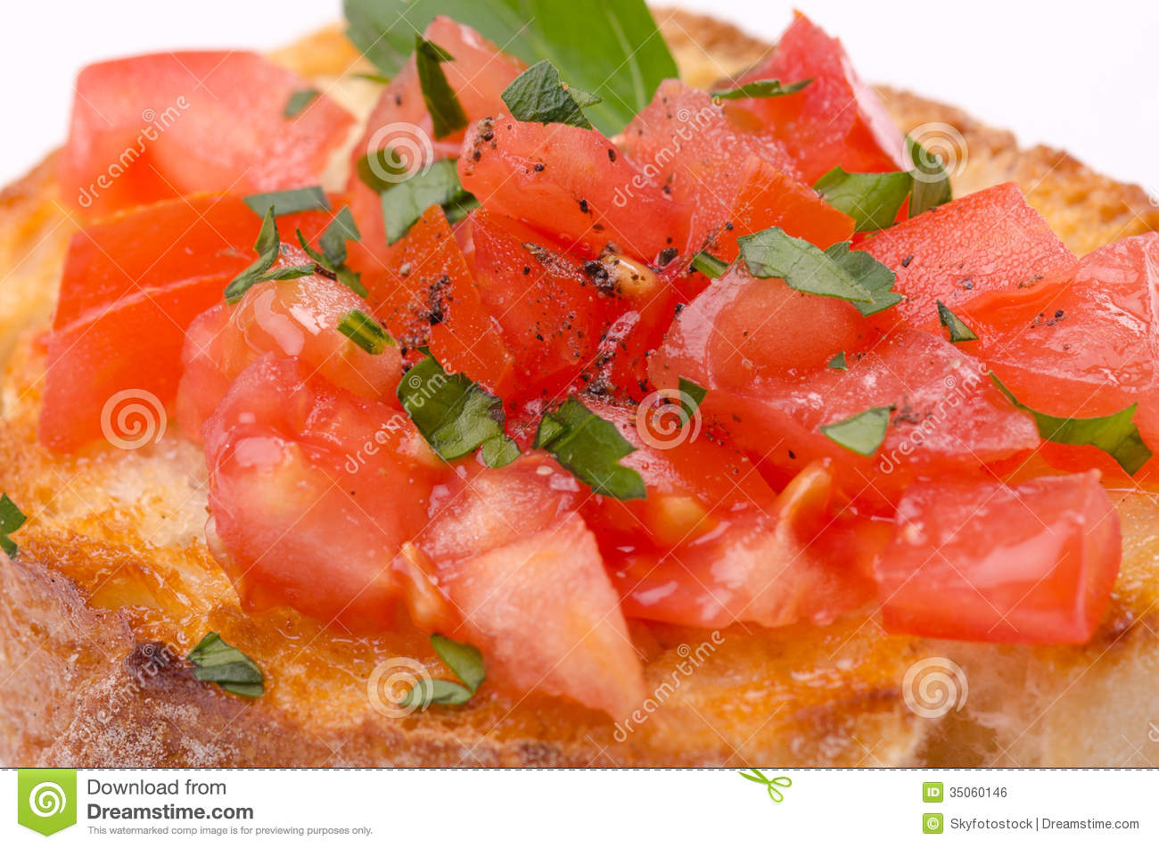 Tomato Bruschetta with olive oil, garlic and fresh basil leaves close ...