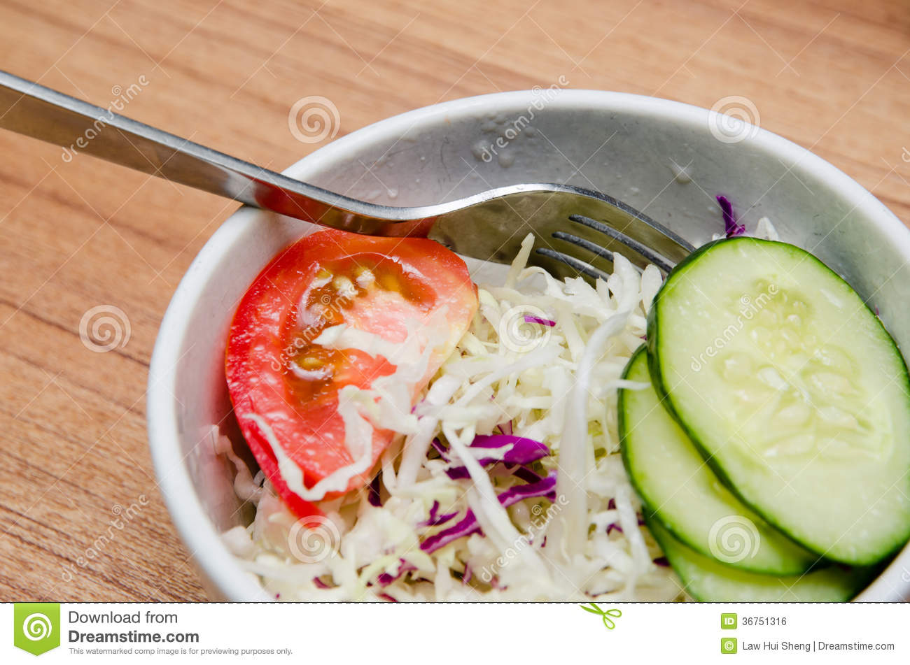 Tomato, cucumber and cabbage salad in a white bowl. By Law Hui Sheng .