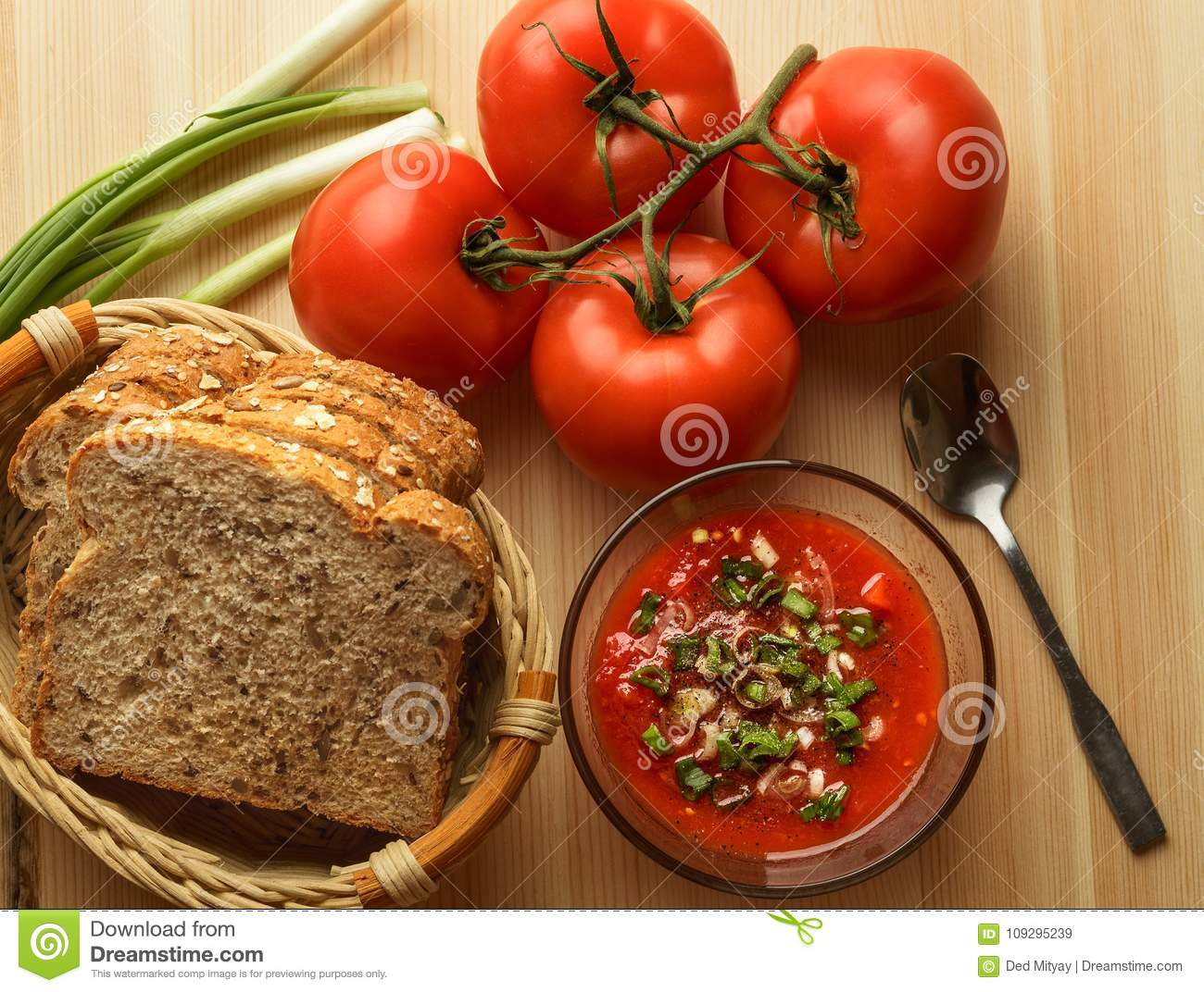 Tomato sauce in glass bowl, fresh bread, onion on wooden table, sauce ingredients for homemade vegetarian food, top view