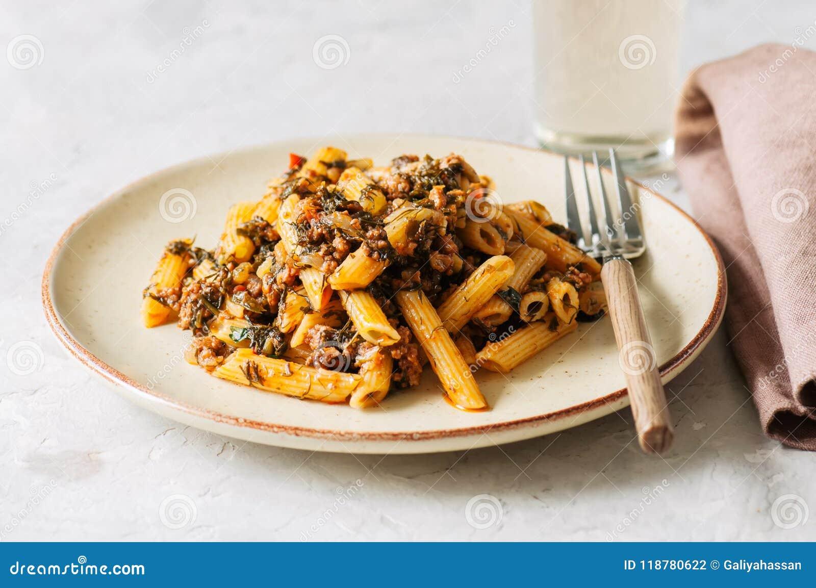 Tomato sauce ground beef pasta on a white stone background. Tone