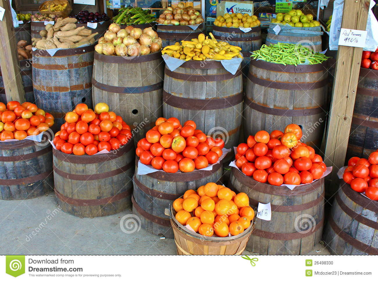 Tomatoes and other produce form a colorful display in front of an old ...