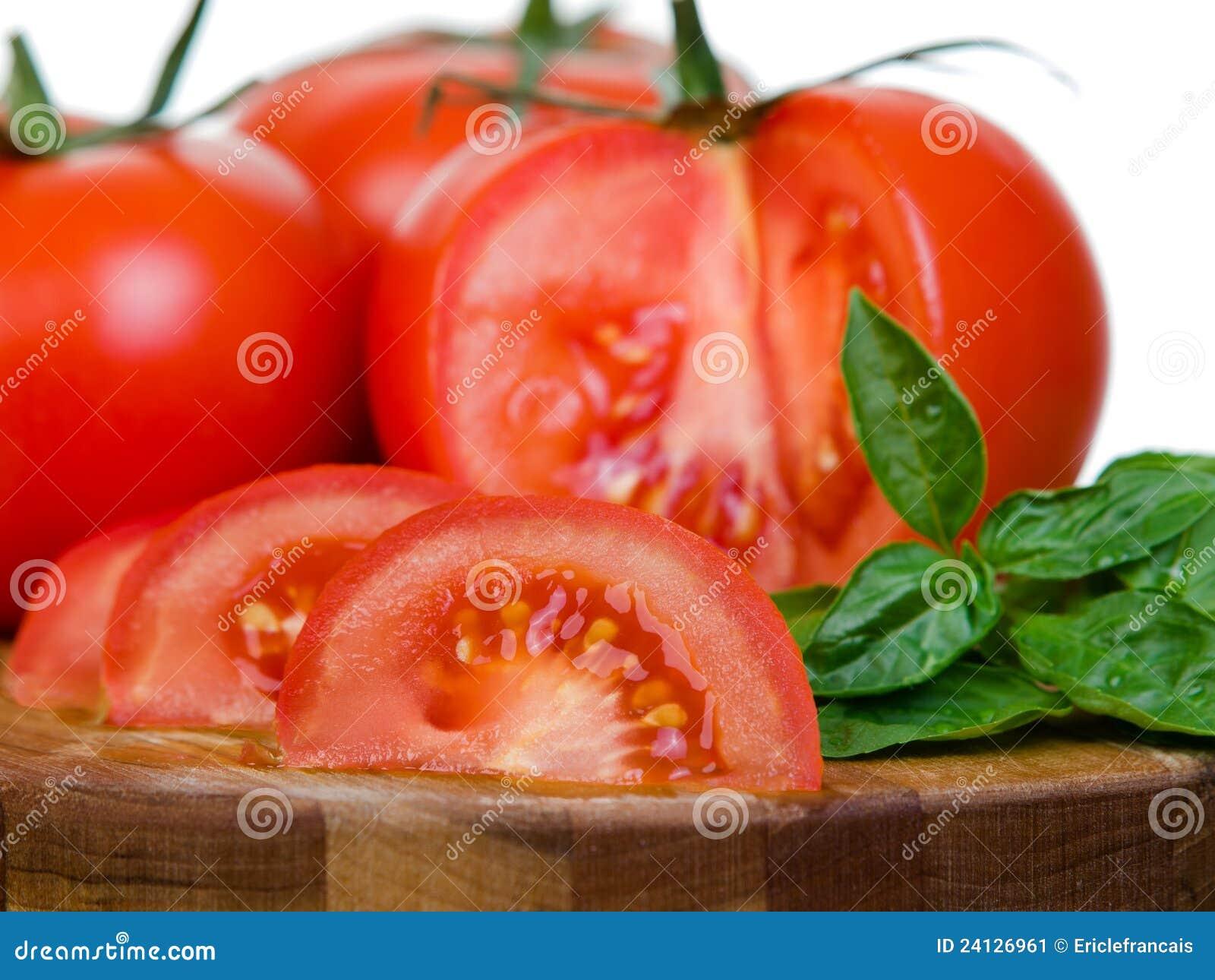 Tomatoes presentation sliced on wooden plank macro stock