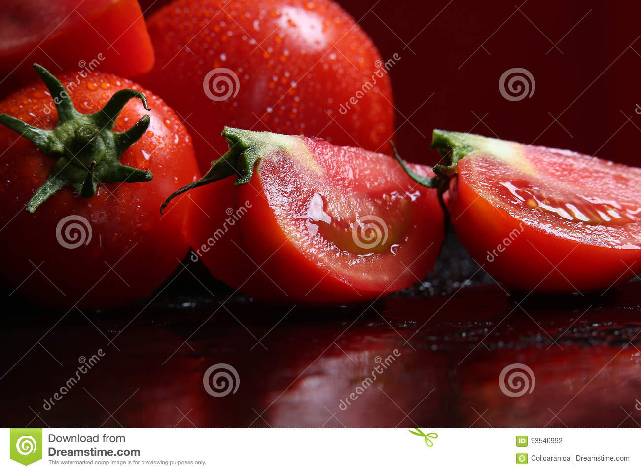 Tomatoes under water drops, red background