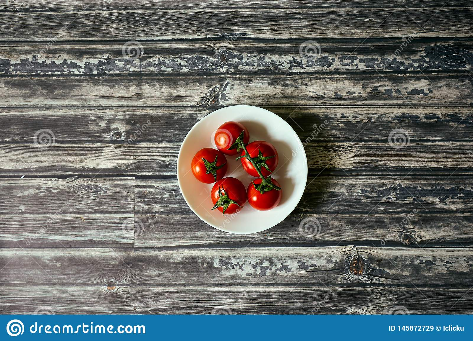 Tomatoes in a white circular bowl from top down. In a dark wood background royalty free stock images