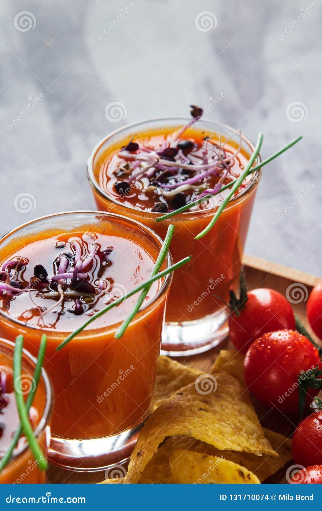 Tomatsoppagazpacho i exponeringsglas med spirade groddar som medföljs med havrechiper på ljust - grå bakgrund vertikalt Banta och