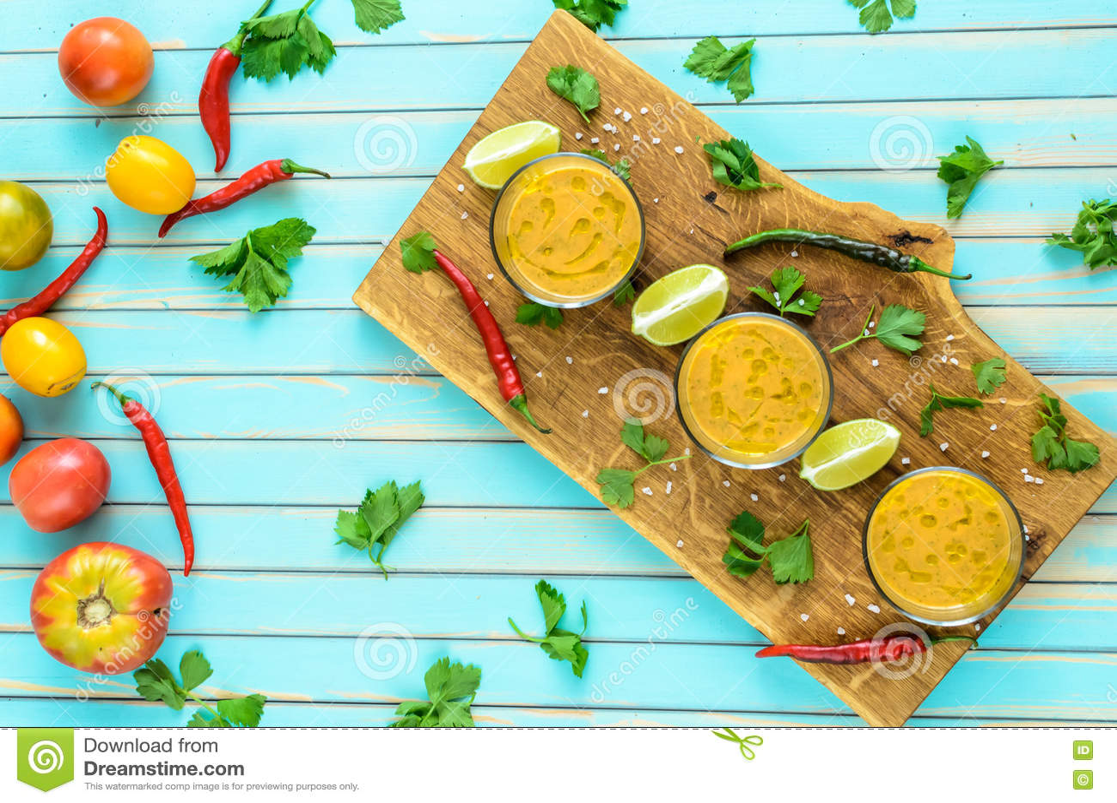Tomatsoppagazpacho och ingredienser över turkosträbakgrund