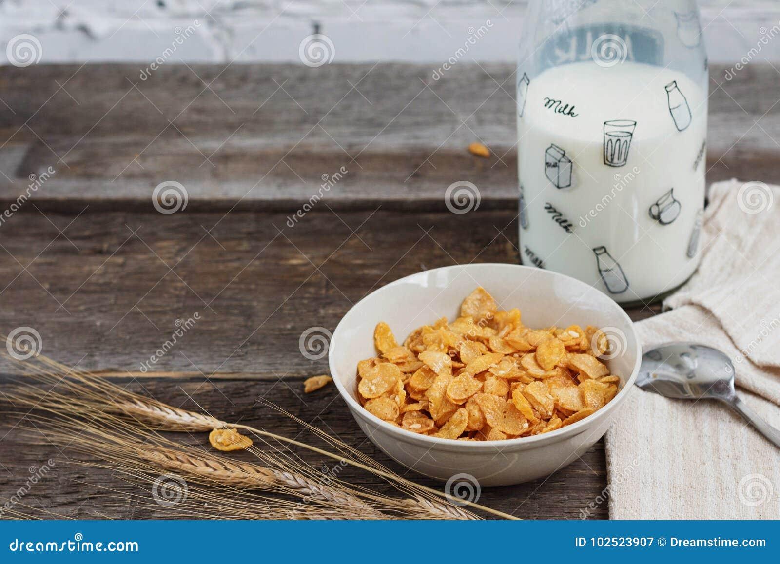 Tome o café da manhã com os flocos de milho com leite e suco de laranja em uma tabela de madeira