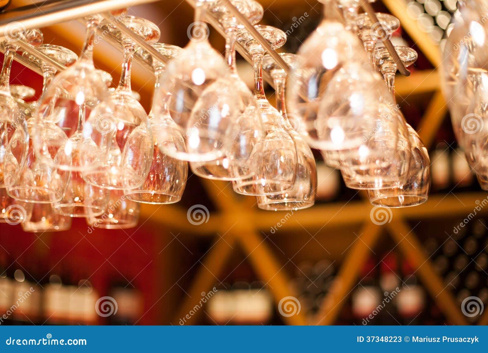Tomma exponeringsglas för vin ovanför en stång rack