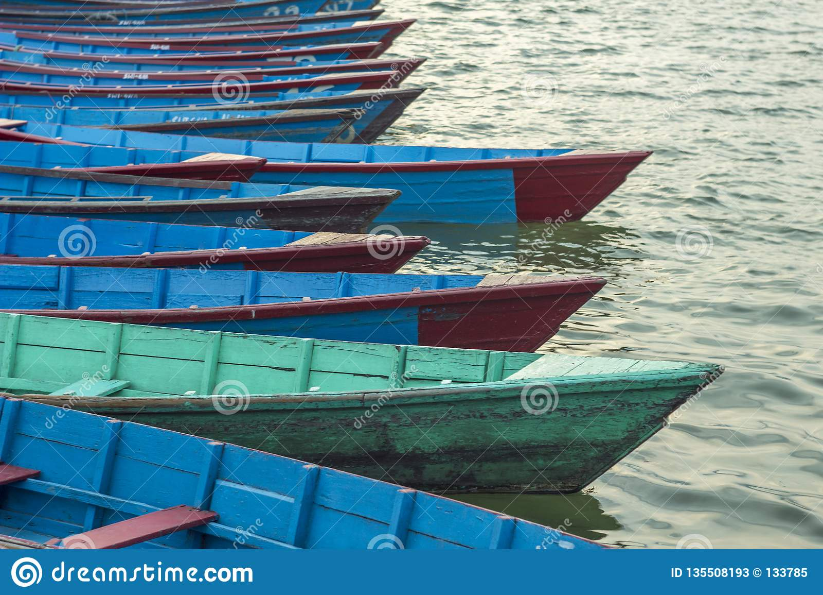 Tomma gamla träblåa röda gröna fartyg på vattenställningen i rad