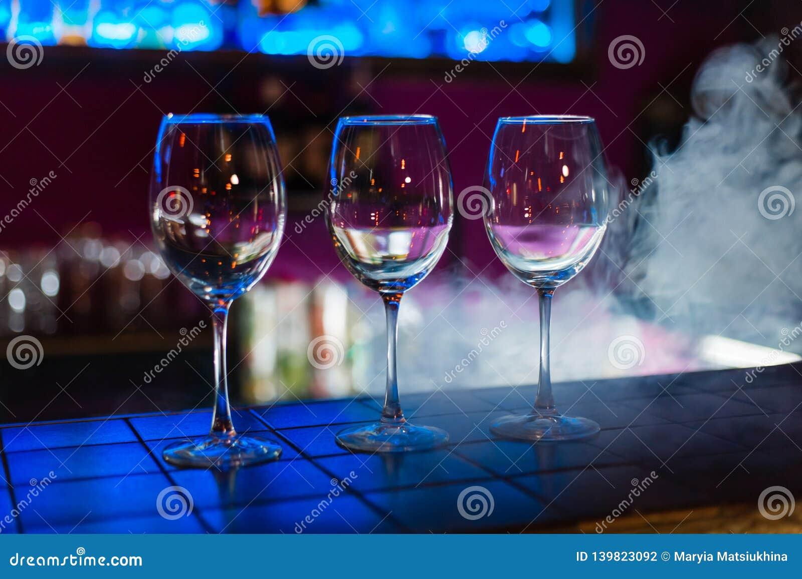 Tomma vinexponeringsglas i rad på stång eller restaurang