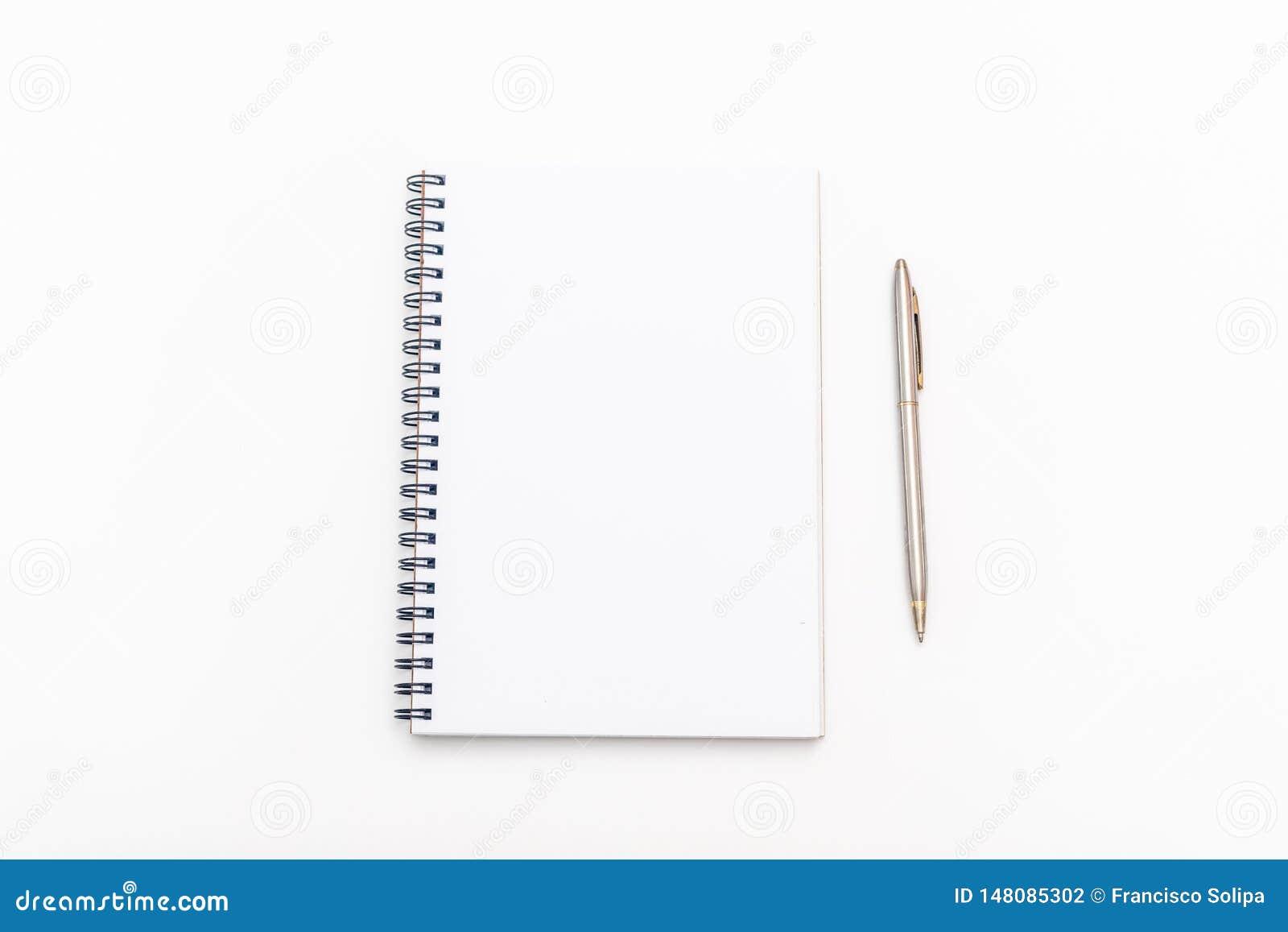 Tomt ark av anteckningsboken med en spiral och pennan på en vit bakgrund kopiera avst?nd