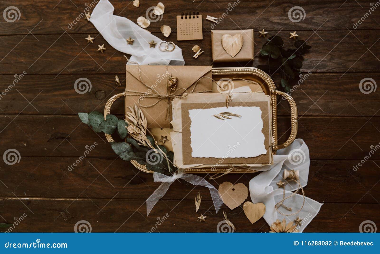 Tomt hälsningkort med kraft kuvert- och guldgarneringar på träbakgrund gifta sig för trappa för stående för brudbegreppsklänning