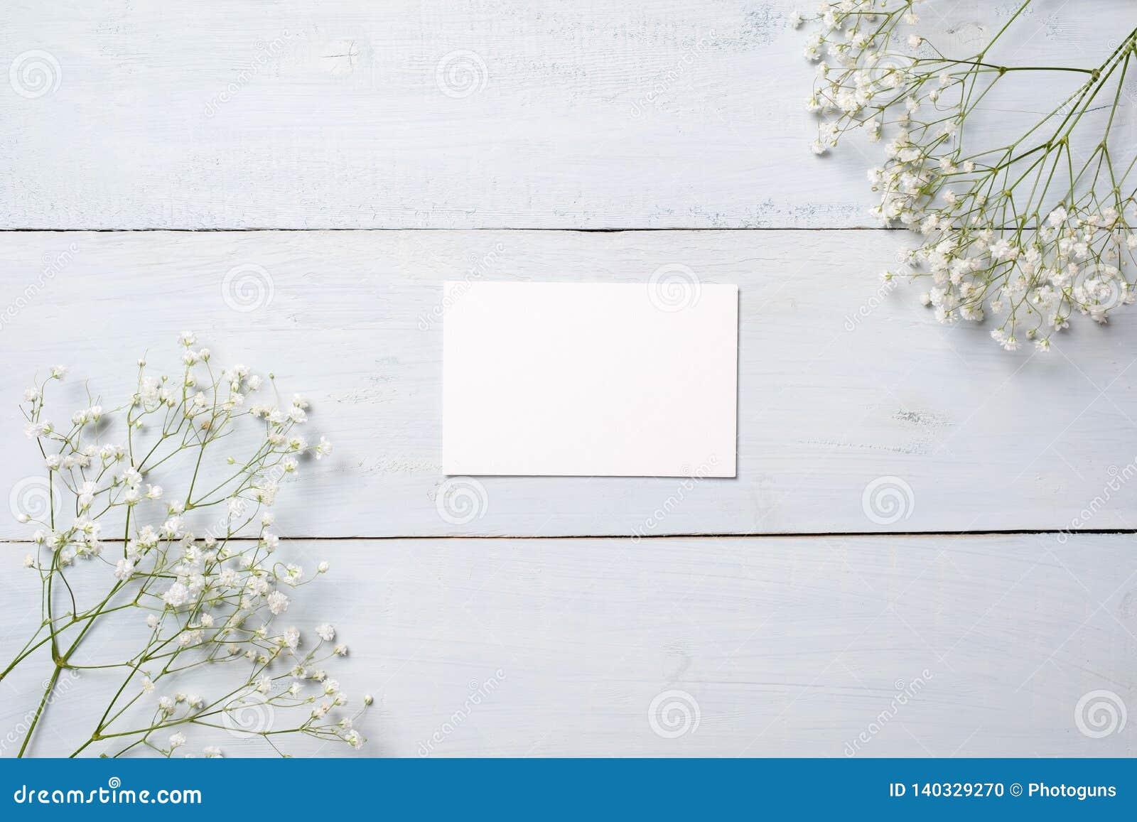 Tomt kort på det blåa träskrivbordet med blommor Tomt hälsa kort för din lyckönskan med den påsk-, moder- eller kvinnas dagen, vå