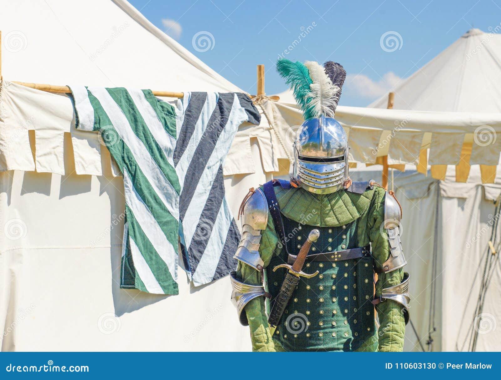 Tomt pansar för riddare` s framme av vita tält i bakgrunden
