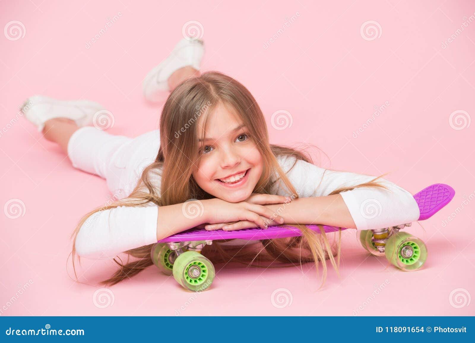 Tonårhobbybegrepp Flickan gillar för att rida skateboarden och sportig livsstil Flicka på att le framsidan som poserar med encent