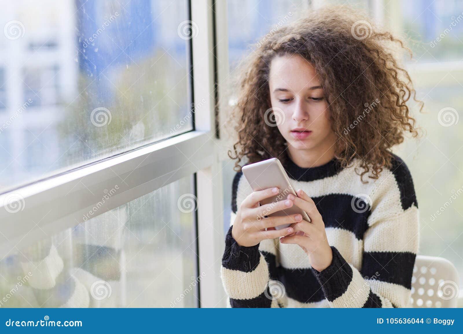 Tonårig flicka för lockigt hår med mobiltelefonen vid fönstret