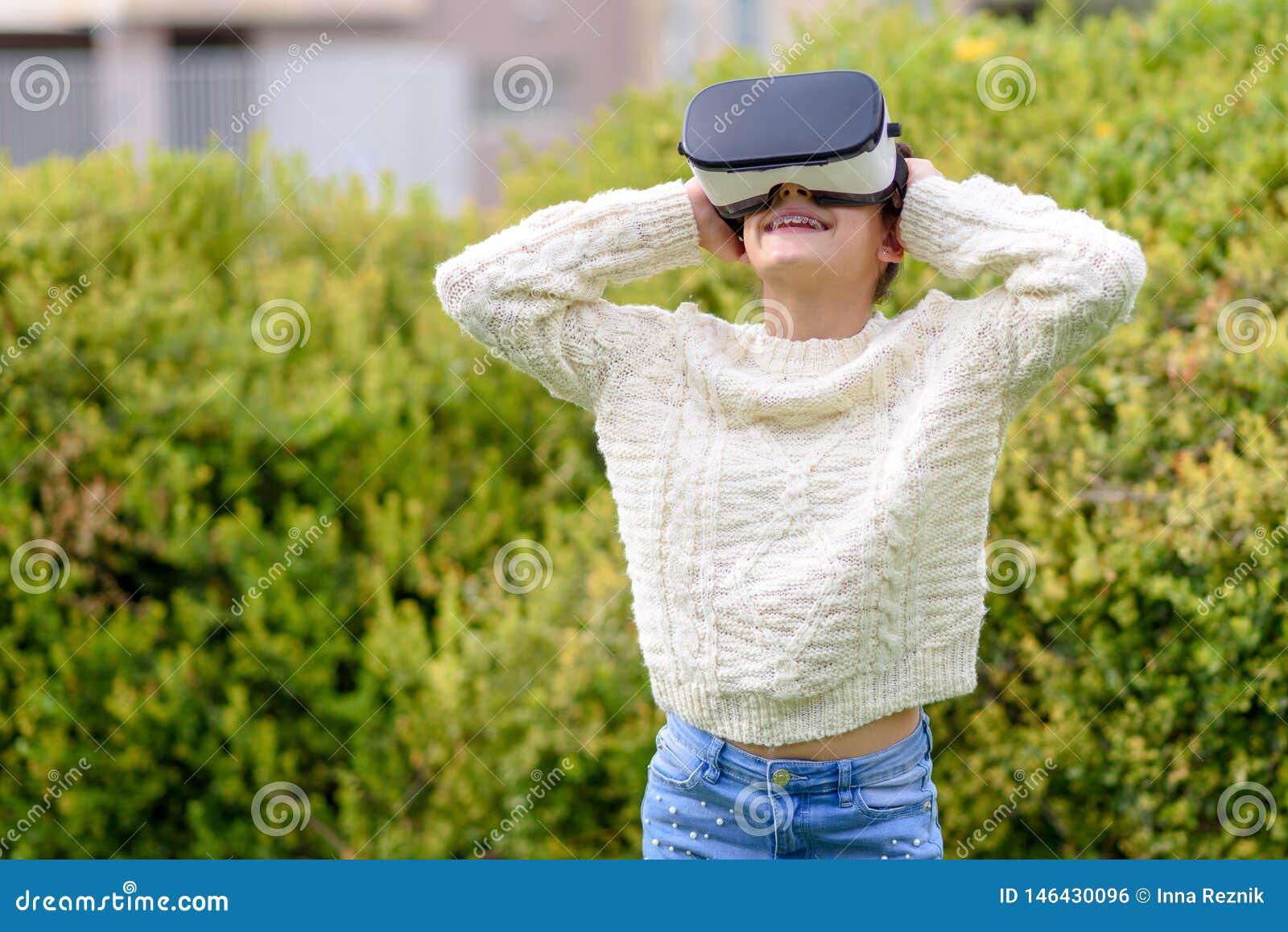Tonårig flicka med virtuell verklighethörlurar med mikrofon