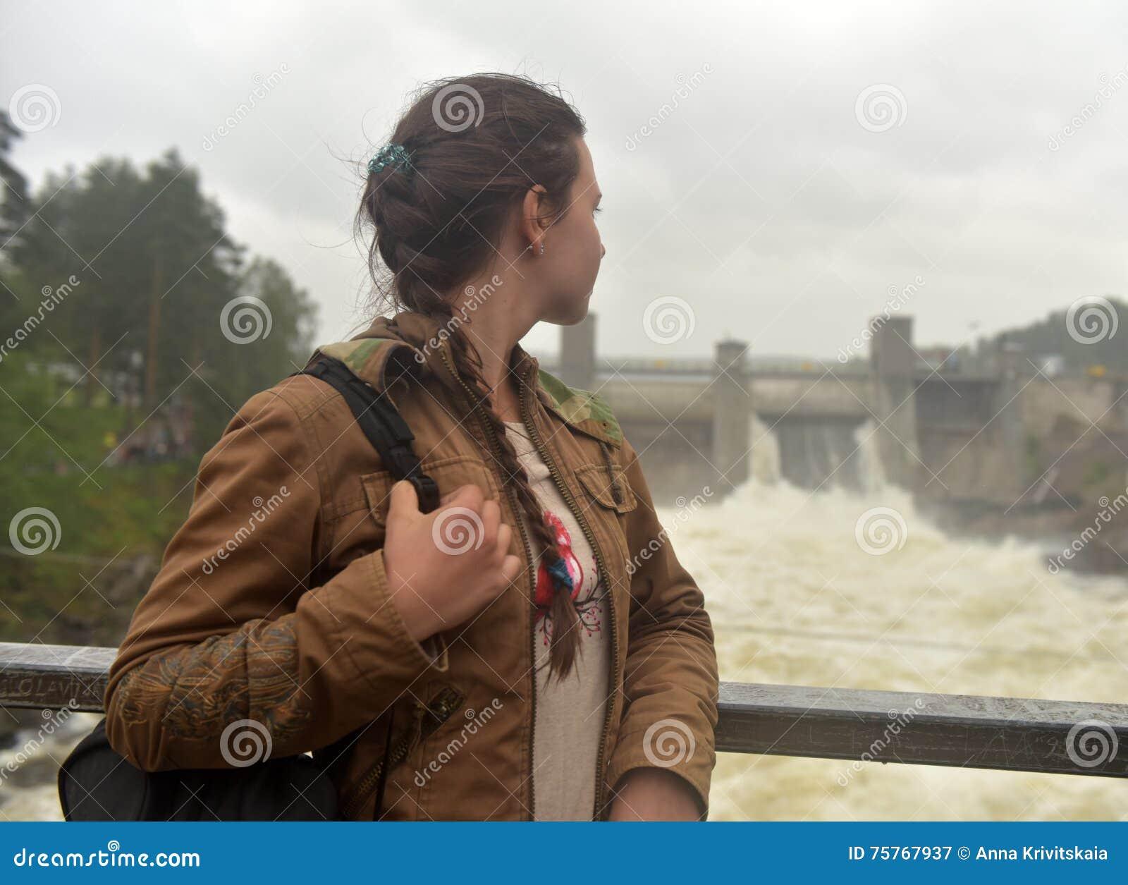 Tonårig flicka på bakgrund av kraftverket i Imatra