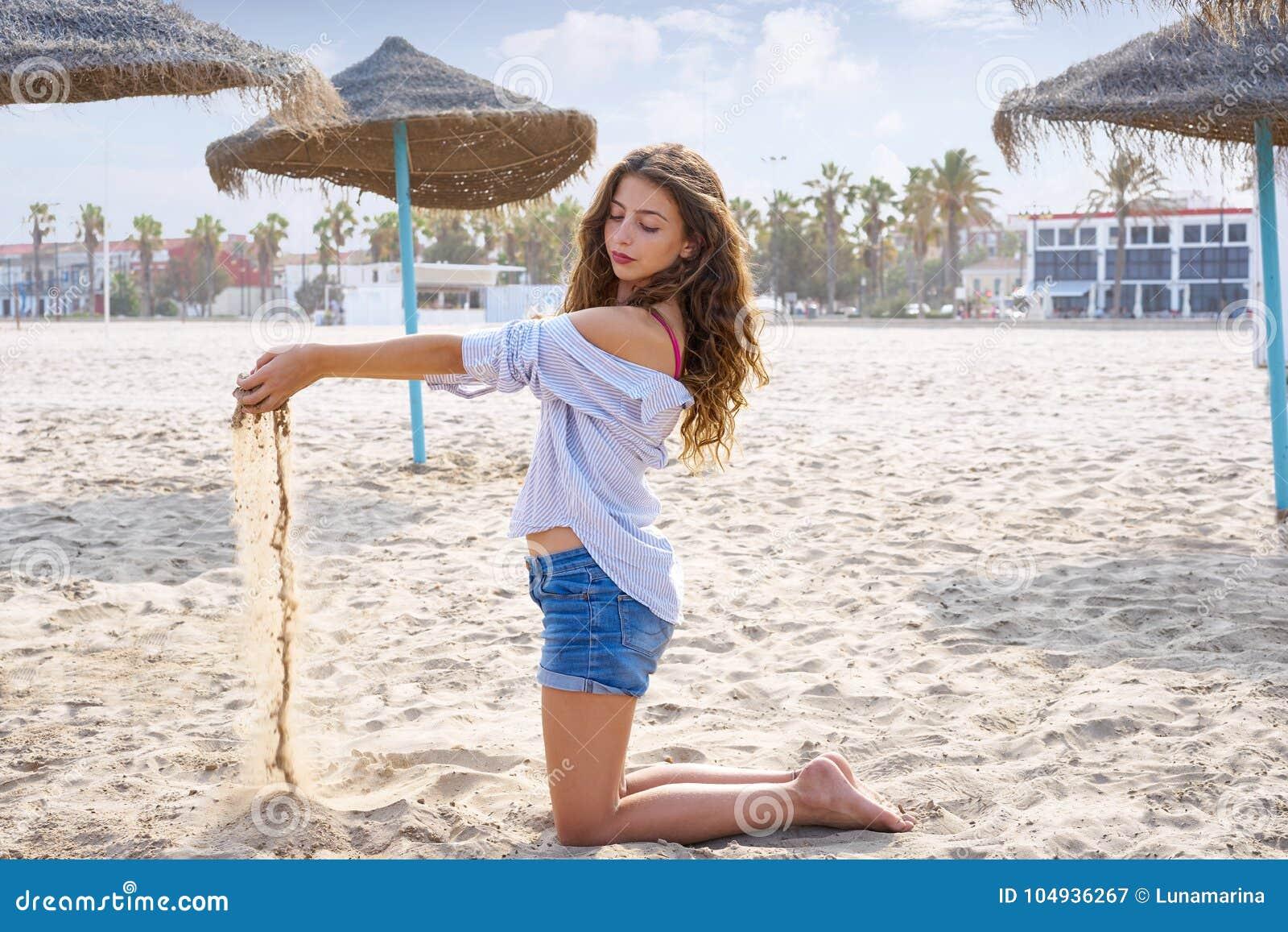 Tonårig flicka på stranden som spelar med sand