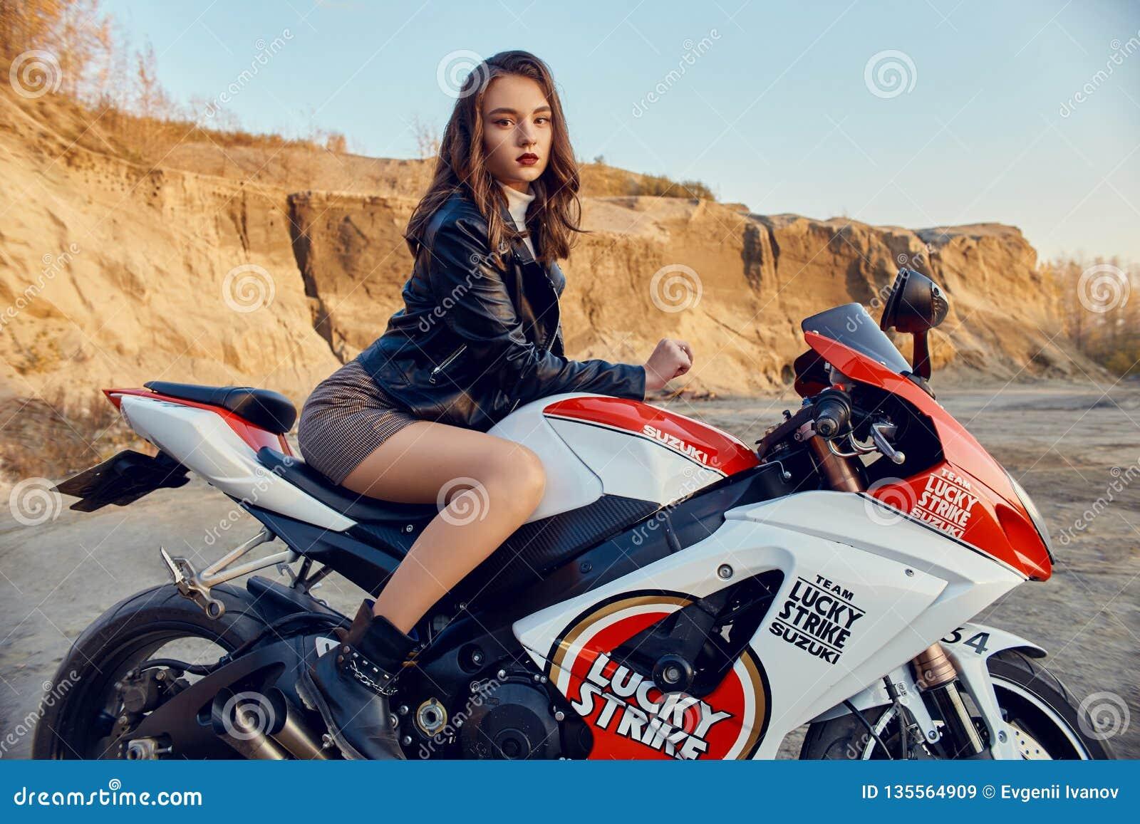 Tonårig flicka som sitter på en tävlings- motorcykel, härlig sexig cyklist i en kort kjol på en sportmotorcykel i natur En vän av