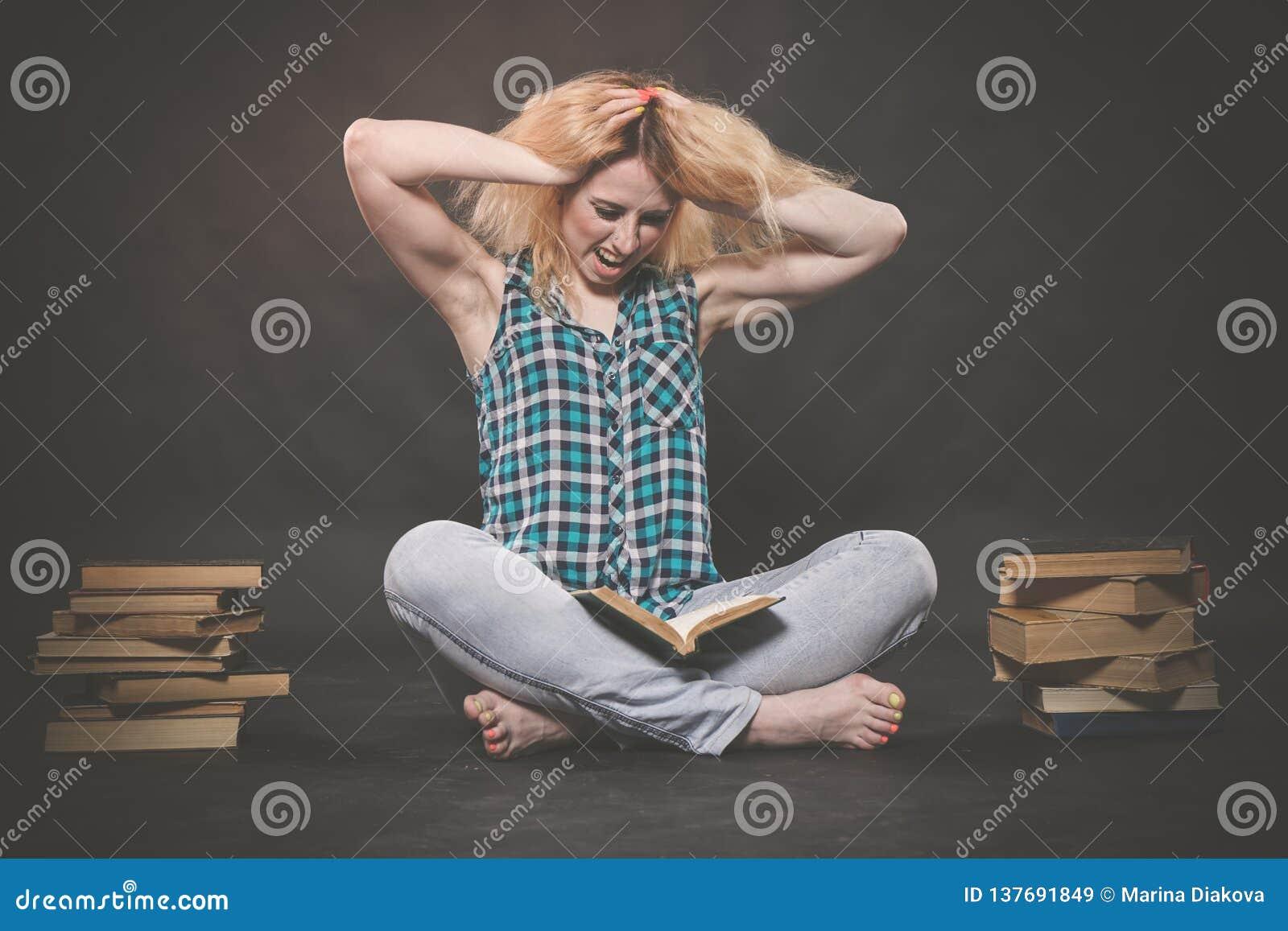 Tonårig flicka som sitter på golvet bredvid böcker och visar känslomässigt hennes hat, hat och trötthet
