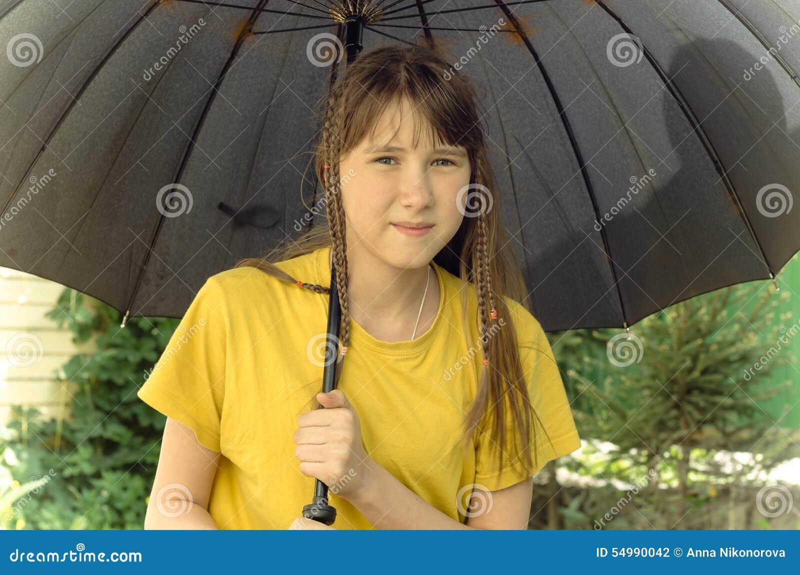 Tonårig flicka under det stora paraplyet