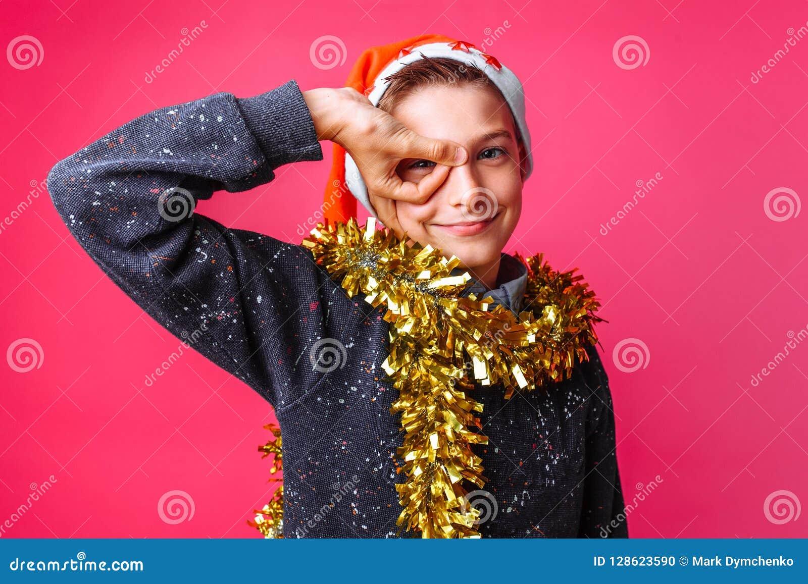 Tonårig grabb i hatt för jultomten` s och med glitter på hans hals, reko si för shower