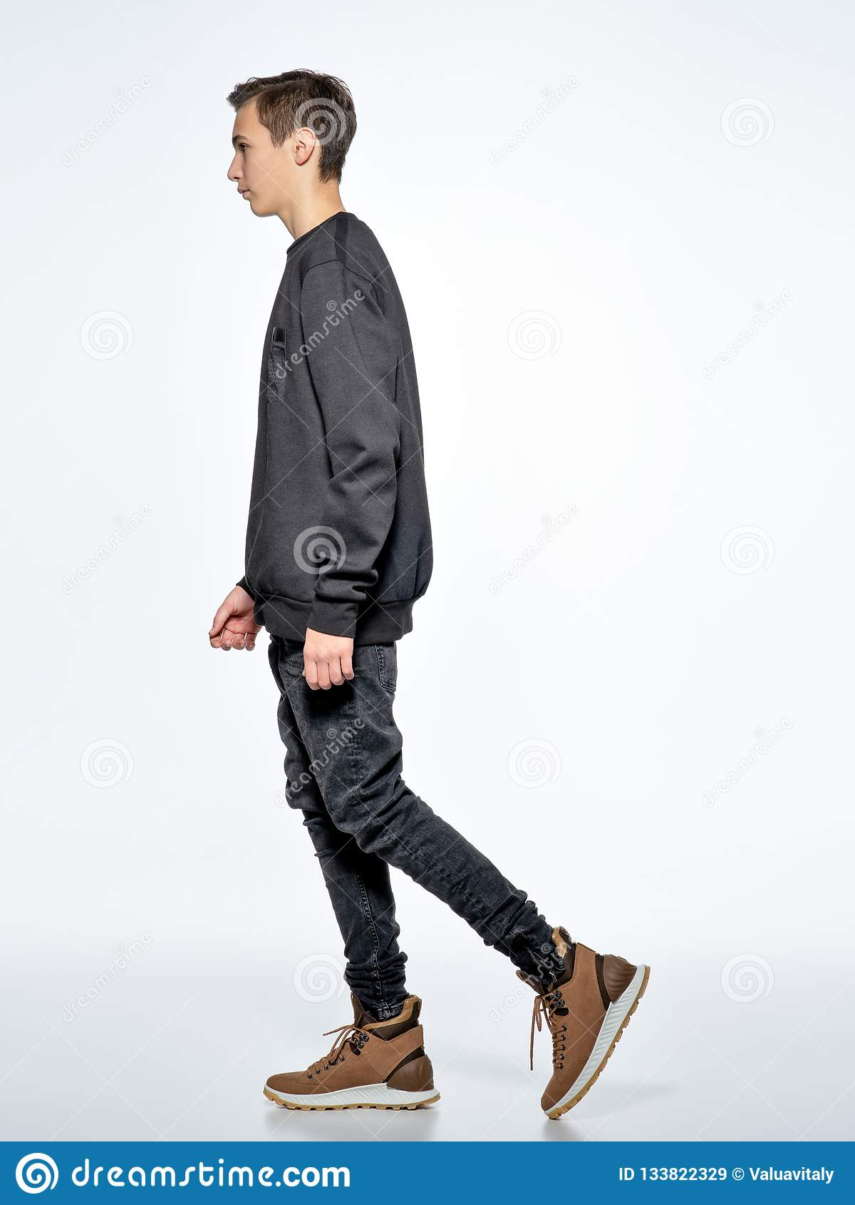 Tonårig pojke som poserar på studion Gå by