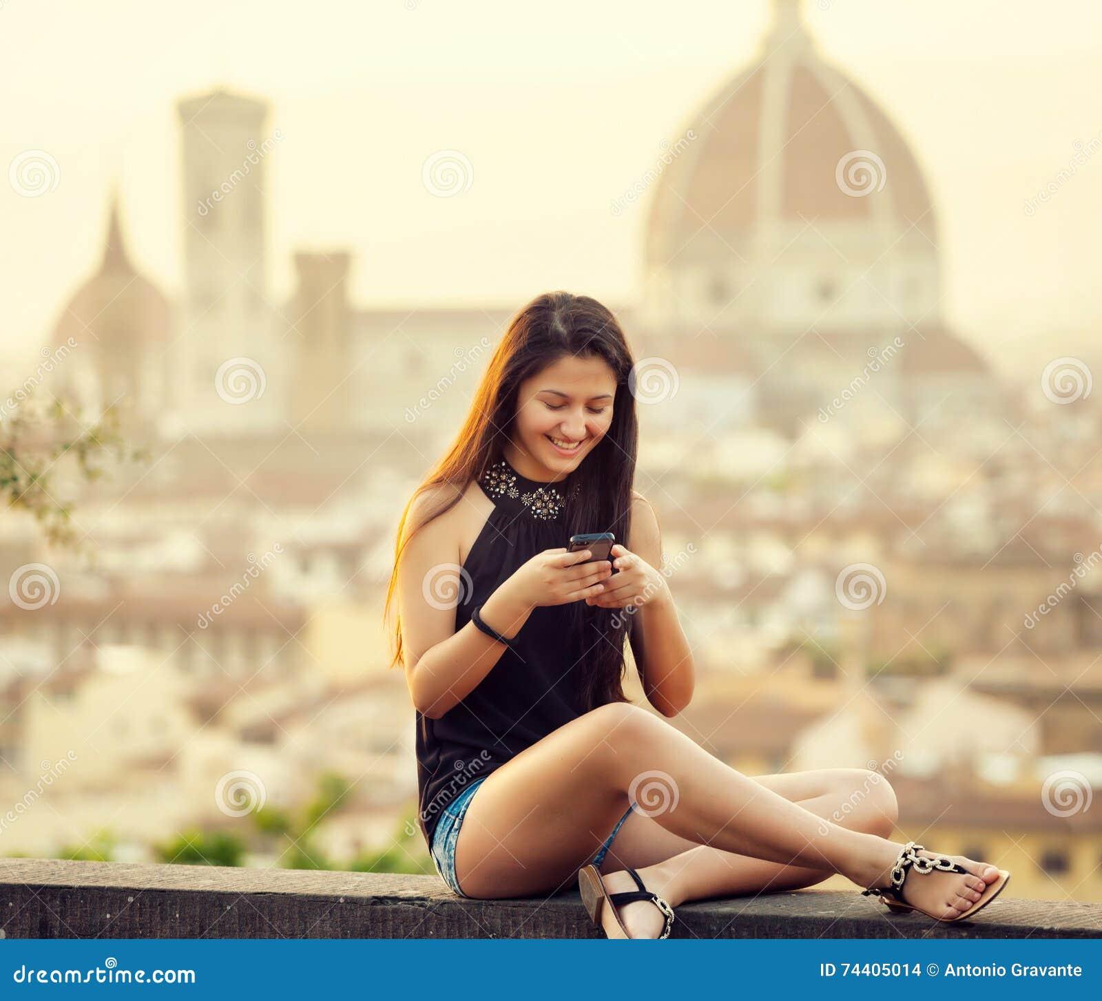 Tonårigt på solnedgången i Florence använder smartphonen