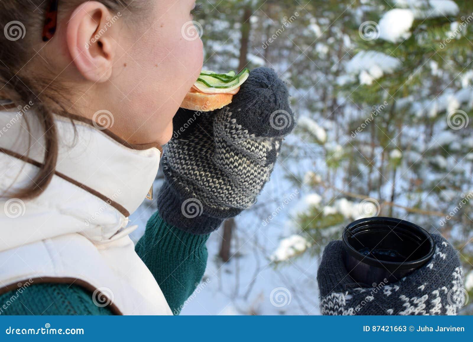 Tonåring som äter smörgåsen i vinterskog