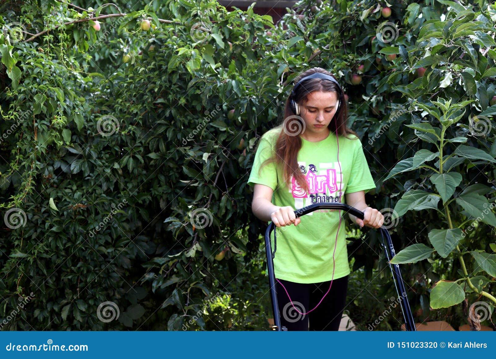 Tonåring som mejar gräsmatta som omges av äppleträdet