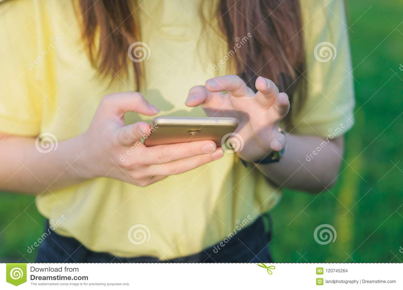 Tonåring som trycker på en skärm Kvinna som rymmer en mobiltelefon i händer