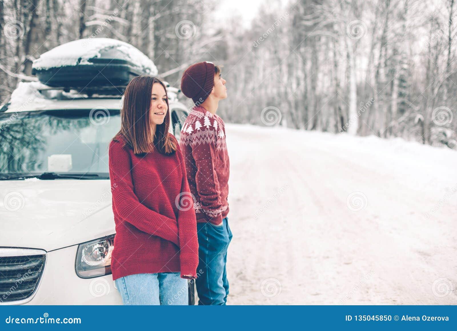 Tonåringar i jultröjor som går i insnöad vinter