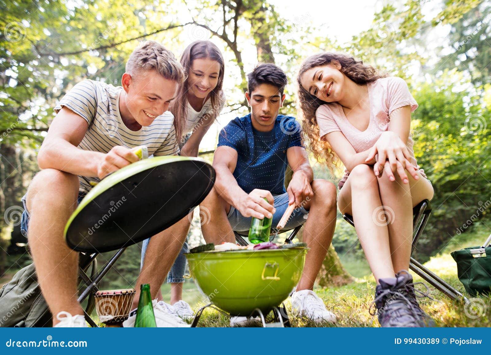 Tonåringar som campar och att laga mat kött på grillfestgaller