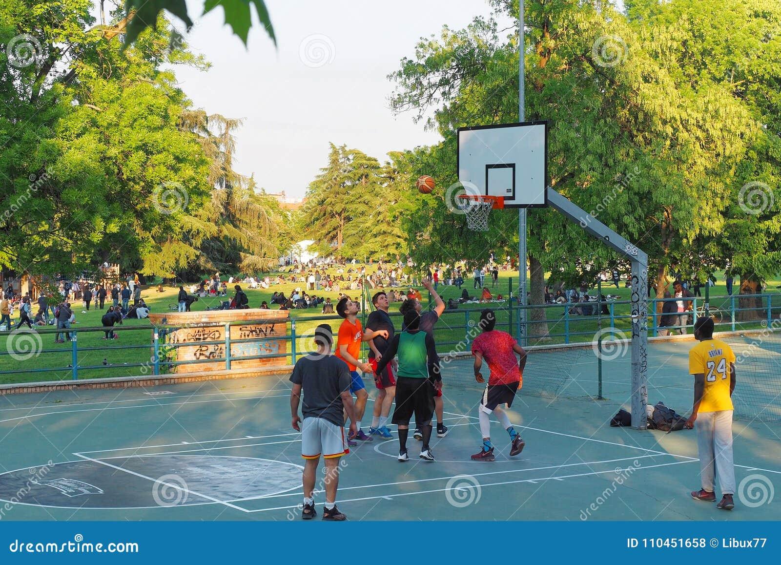 Tonåringar som spelar basket på staden, parkerar