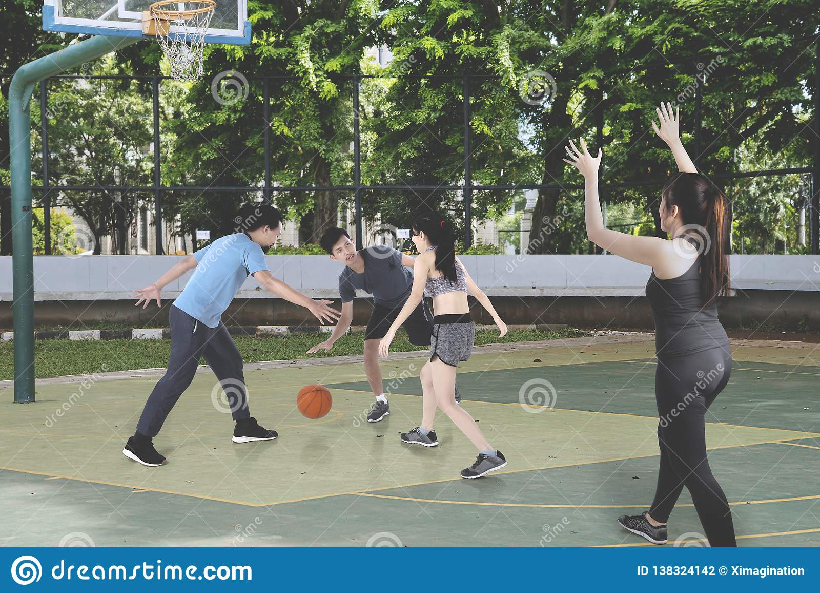 Tonåringar som spelar basket tillsammans på det fria