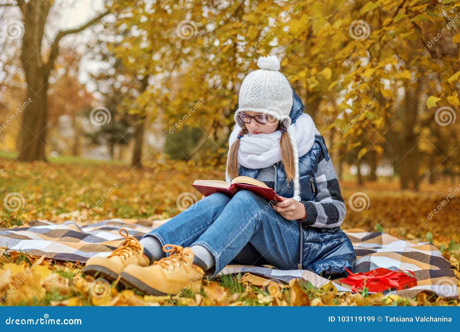 Tonåringelevflickan i exponeringsglasstudielärobok i parkera sitter på en pläd i en hemtrevlig vit halsduk och hatt
