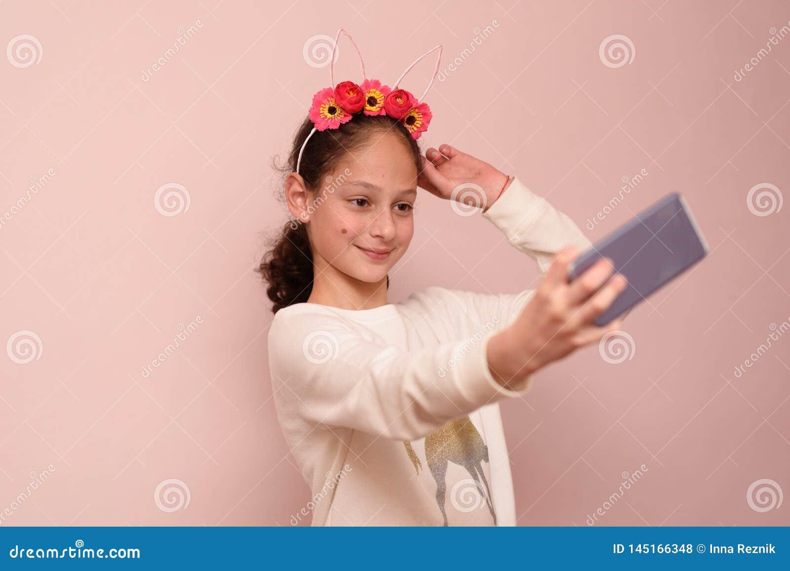 Tonåringflicka med diademen av blommor som tar selfie med hennes mobiltelefon på rosa bakgrund