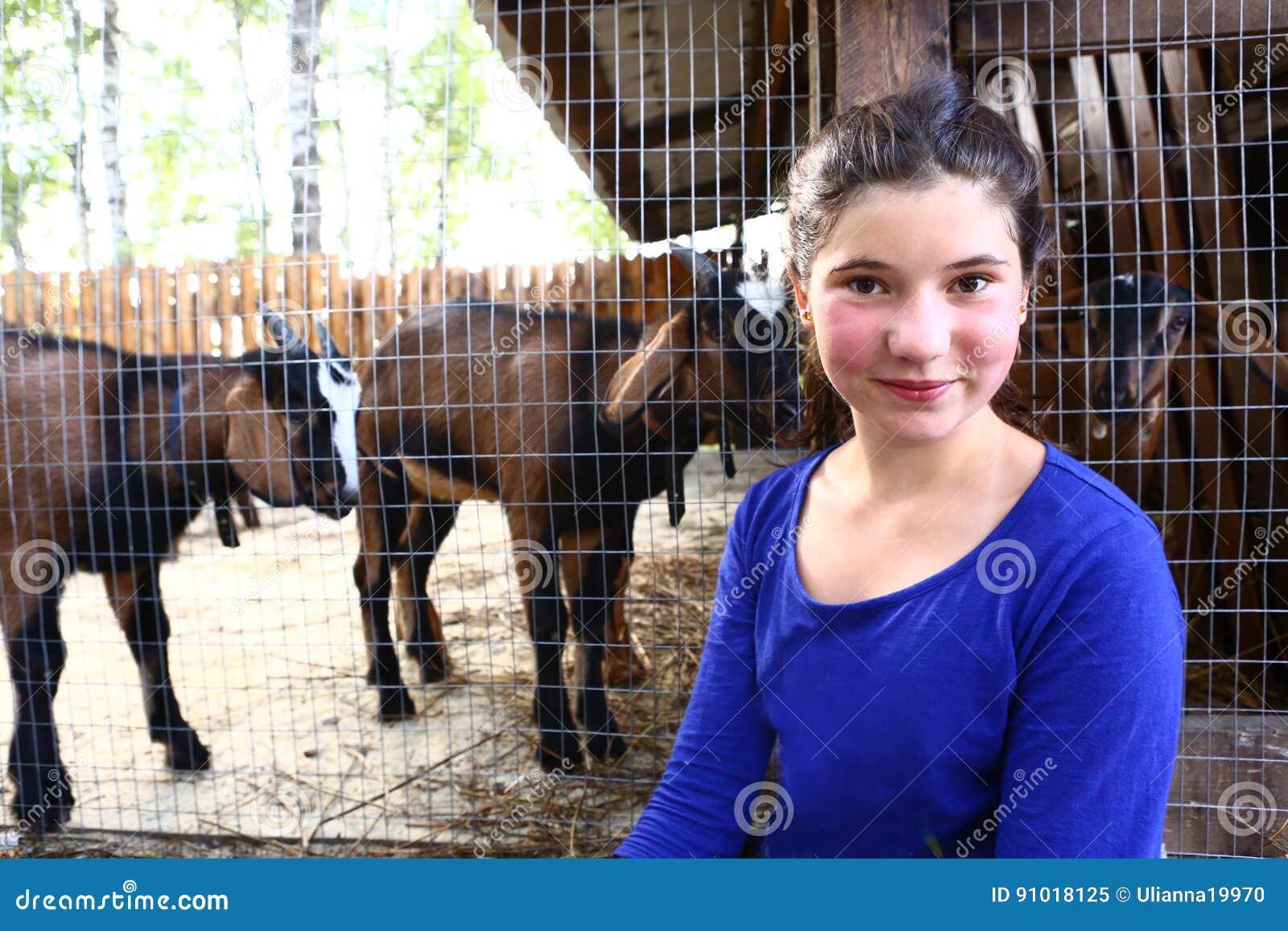 Tonåringflickaslut upp fotoet på zoopuddock med getter