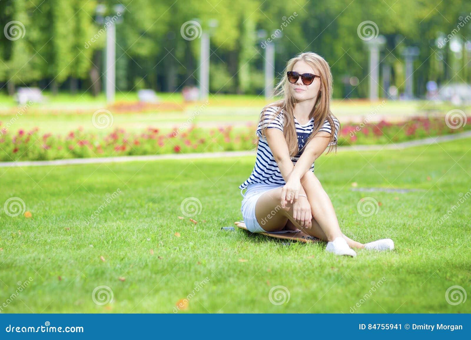 Tonåringlivsstilbegrepp Ståenden av den gulliga och positiva Caucasian blonda tonåringflickan som poserar på Longboard i grön som