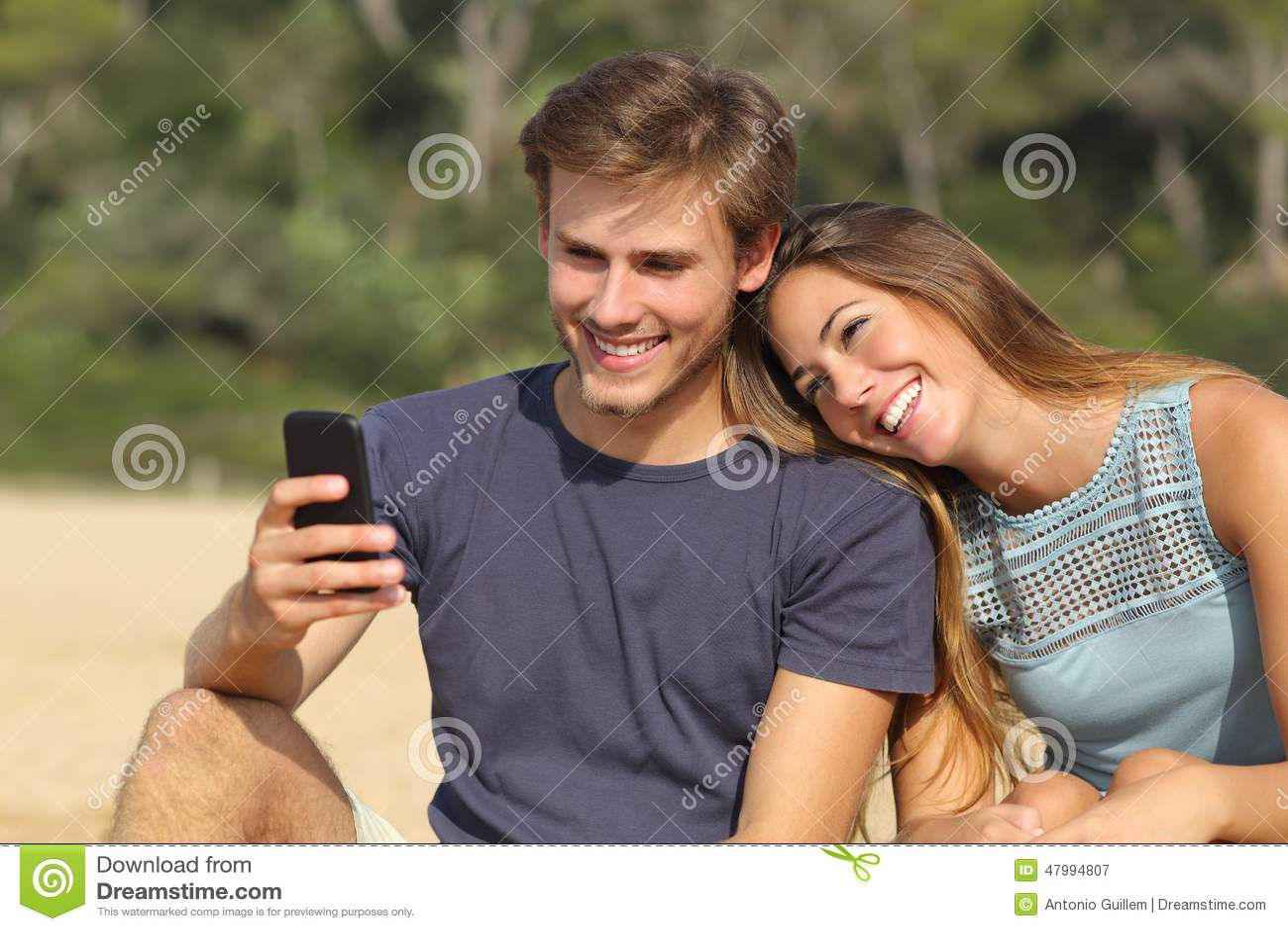 Tonåringpar som delar socialt massmedia på den smarta telefonen