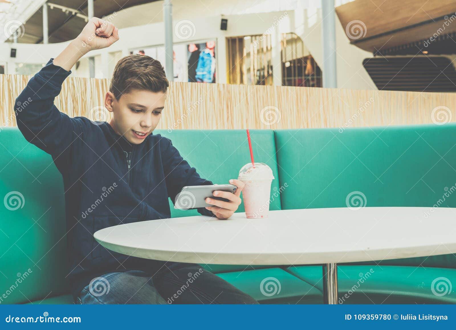 Tonåringpojken sitter på kafétabellen, spelar mobila lekar på smartphonen Pojken sitter med hans hand upp, segern, vinst