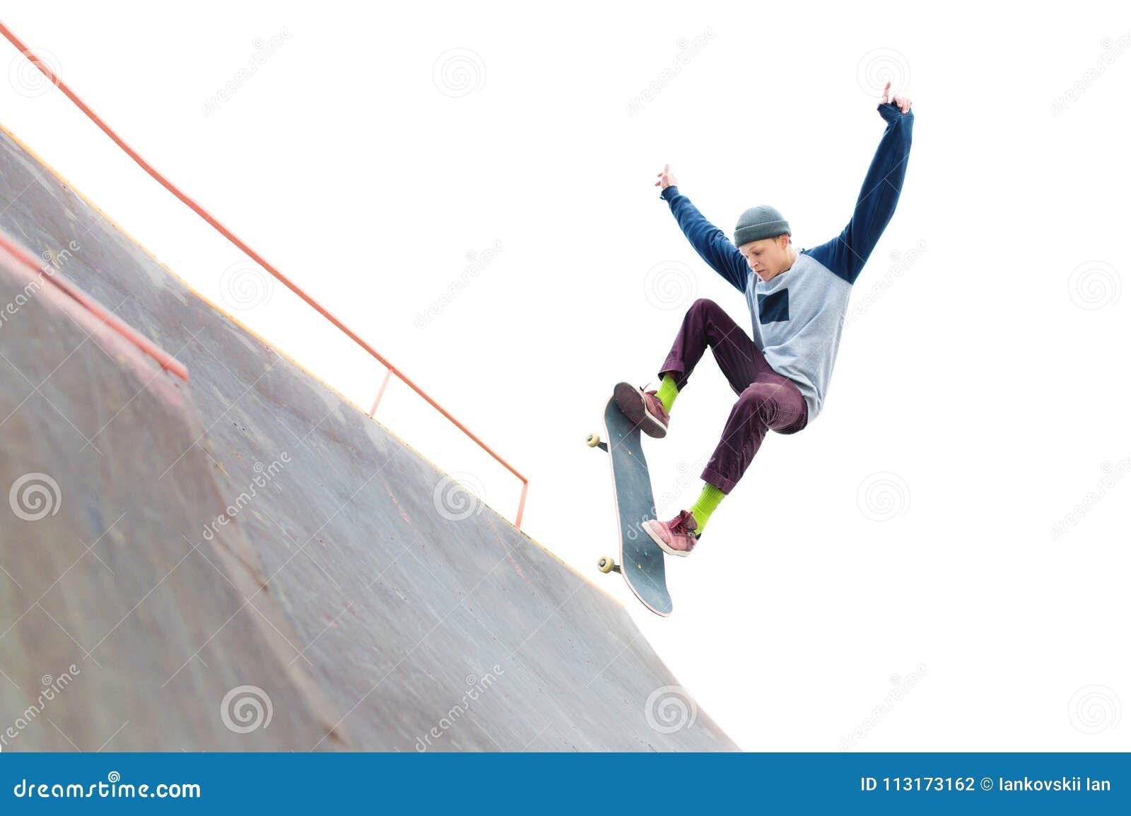 Tonåringskateboarderen i locket gör ett trick med ett hopp på rampen i skateparken Isolerad skateboradåkare och ramp på