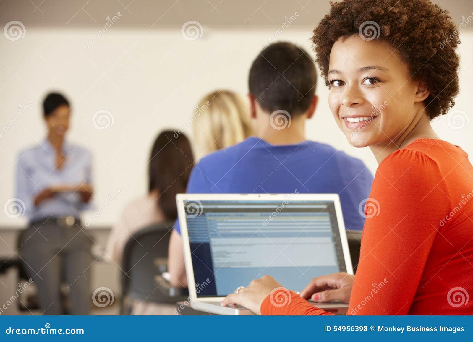 Tonårs- flicka för blandat lopp som använder bärbara datorn i grupp