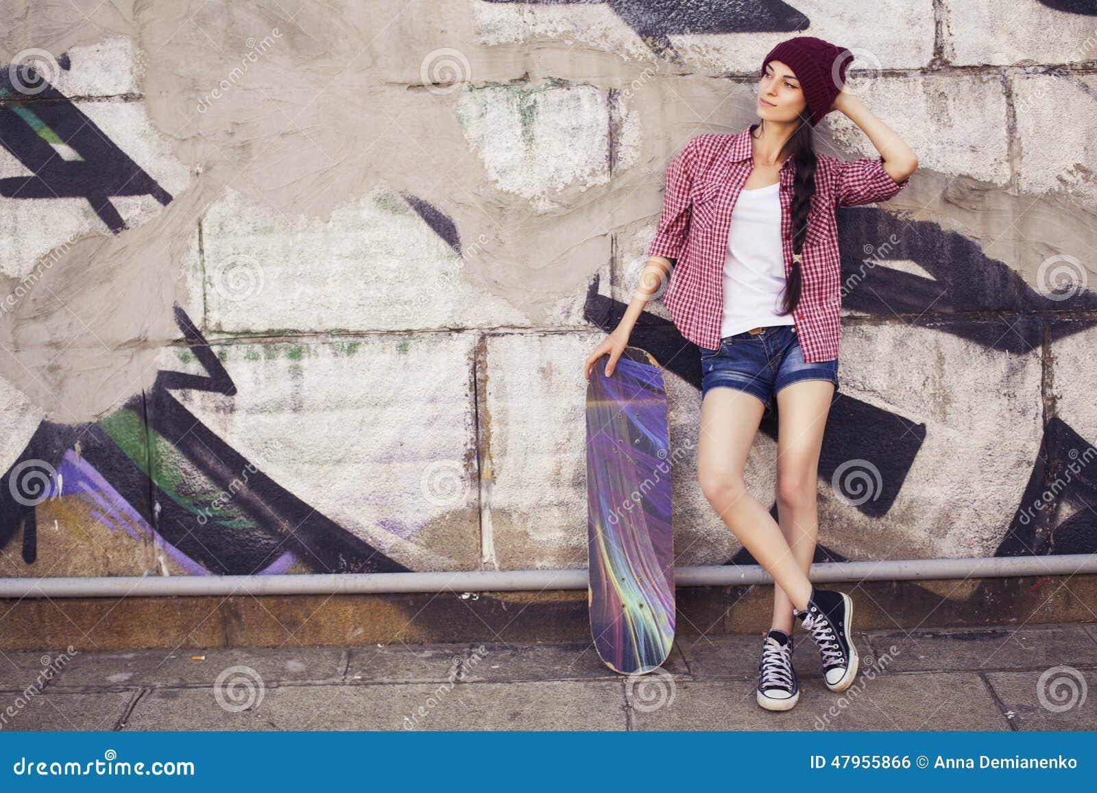 Tonårs- flicka för brunett i hipsterdräkt (jeans kortsluter, keds, plädskjorta, hatt), med en skateboard på parkera
